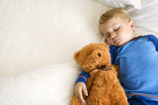 Child sleeping with bear.